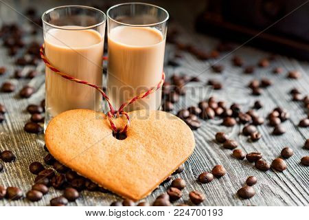 Two shots of cream liqueur with coffee beans on wooden table. Festive concept. Intime mood. Love and Valentine's day romantic atmosphere