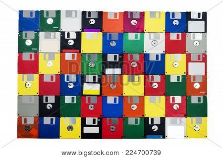 Horizontal shot of a group of multicolored plastic diskettes laid in a solid background with a white background.  Shows fronts and backs of disks.
