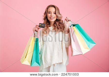 Photo of smiling young woman standing isolated over pink background. Looking camera holding shopping bags and credit card.