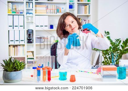 Scientist or researcher researching in the laboratory. Different reagent flasks and test tubes with colored chemical reagents on the laboratory work table.