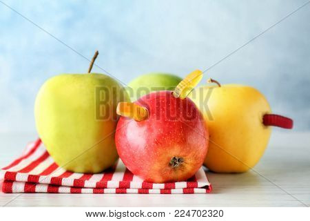 Apples with gummy worms on table. April fools food