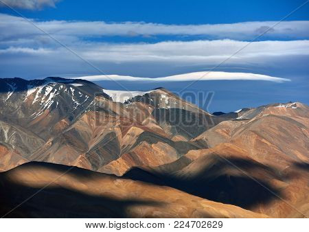 Different bright colors of the mountain valley, alternating black and orange strata of sedimentary rocks, white sky with stripes of white clouds.