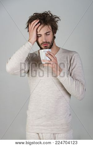 Morning with coffee or milk. Man with disheveled hair drink mulled wine. Sleepy guy with tea cup on grey background. Insomnia, refreshment and energy. Cold and flu, single.