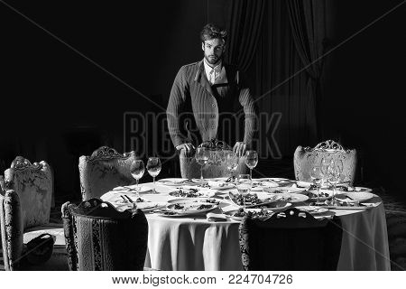 Handsome Young Man With Beard And Blond Hair Stands Over Table With Leftovers Or Residues Food On Di