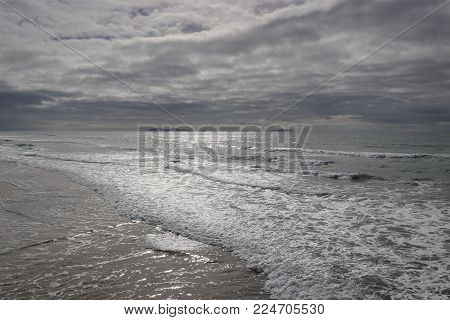 Looking south from the Silver Strand State Beach, Coronado, California, across the sea to the Coronado Islands in Mexico on an unsettled day with a stormy sky,