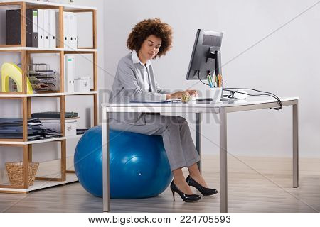 Businesswoman Sitting On Fitness Ball Working On Computer