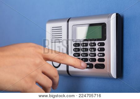 Close-up Of A Person's Hand Entering Code In Security System