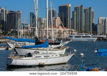San Diego, California, USA - June 6, 2014 - view across the busy harbor with its moored boats to the pink City Administration Building, visitors, and many high rise buildings on a sunny day in America's Finest City.
