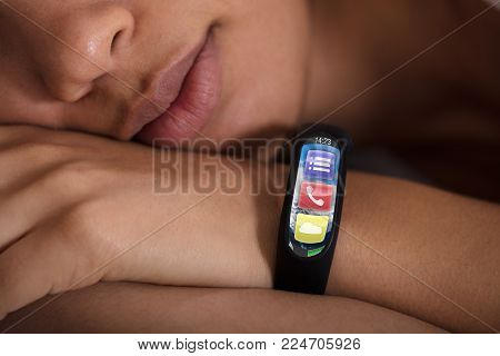 Close-up Of Smartwatch Showing Heartbeat Rate On Sleeping Woman's Hand