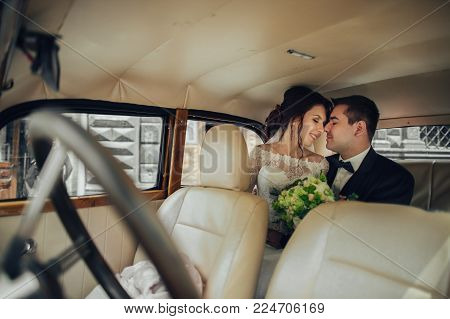 luxury elegant wedding couple kissing and embracing in stylish black car. unusual view in mirror. gorgeous bride and handsome groom in retro style