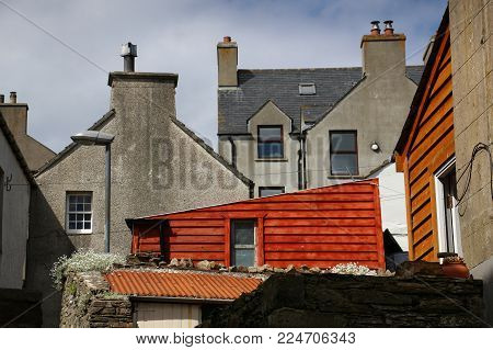 Colorful view of buildings in Stromness, Orkney Island, Scotland, UK where occasional bright red or orange buildings interrupt the typical gray buildings and houses.