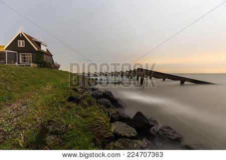 House on the coast of Marken (The Netherlands) surrounded by twelve historical icebreakers. The wooden structures were built in 1872 to provide protection from ice damage.