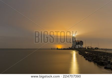 Lighthouse called The Horse of Marken illuminates the night sky over the IJsselmeer lake, The Netherlands. With light reflection on the water surface.