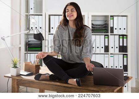 Young Businesswoman Sitting On Wooden Desk Meditating In Office
