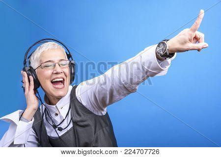 Senior old woman listening to her favorite music through big headphones, enjoying the rich sound
