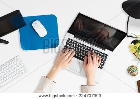 High Angle View Of A Businessperson's Hans Using Laptop