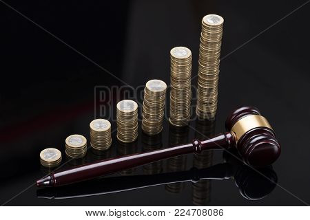 Gavel On Sounding Block In Front Of Golden Stacked Coins Against Grey Background