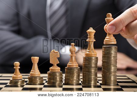 Close-up Of Businessperson's Hand Placing Brown Chess Pieces On Stacked Coins