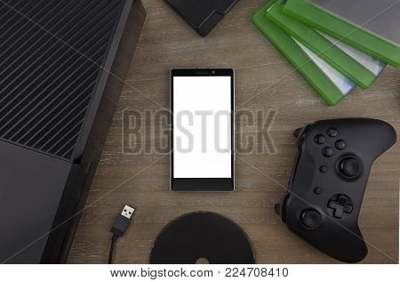 View from the top on smart phone, game console, game pad, game discs and game accessorize laying on the table. You can put any image on a screen.