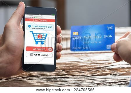 Businessperson's Hand Doing Online Shopping On Smartphone With Debit Card Over Wooden Desk