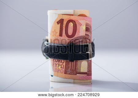 Rolled Up Ten Euro Banknotes Tied With Belt Against White Background