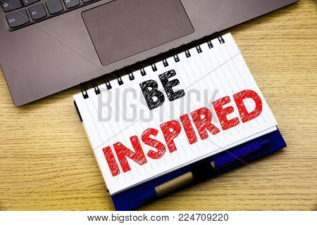 Hand writing text caption inspiration showing Be Inspired. Business concept for Inspiration and Motivation written on notebook book on wooden background in the Office with laptop