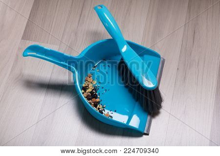 Dirt Collected In Plastic Sweeping Dust Pan And Brush Over The Hardwood Floor
