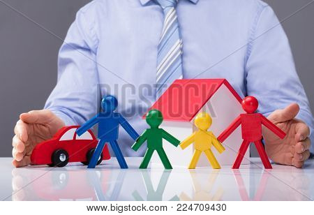 Businessperson Protecting Multi Colored Human Figures, House Model And Car On White Desk