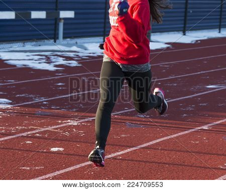 A high school track and field runner is running on an icy and snowy track on a sunny afternoon during practice.
