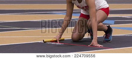 A high school girl is ready to start her rteams elay race in the on your mark position waiting to sprint on an indoor track.