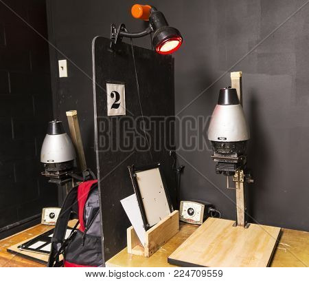 A dark room is set up with old fashion black and white enlargers ready to print pictures.