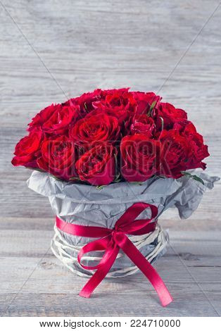Red rose in a vase on a wooden background