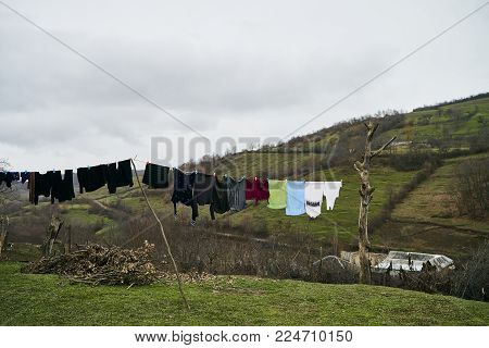 Clothes hanging to dry on a laundry line against green hill with mountain in countryside village