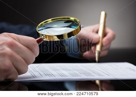 Close-up Of A Businessperson's Hand Checking Contract Form Through Magnifying Glass