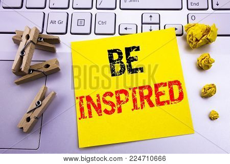 Hand writing text caption inspiration showing Be Inspired. Business concept for Inspiration and Motivation written on sticky paper on the white keyboard background.