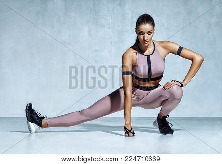 Athlete girl stretching her hamstrings. Photo of young latin girl doing exercising on grey background. Strength and motivation