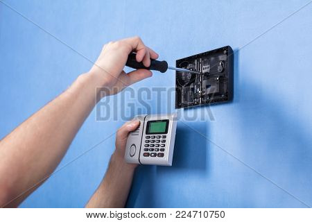 Human Hand Installing Security System On Blue Wall