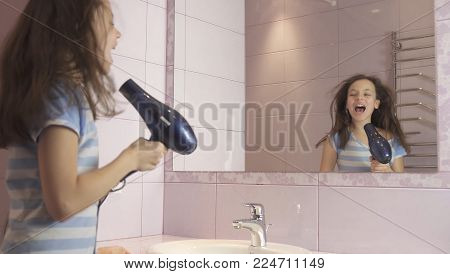 Beautiful happy girl teenager dries hair with a hair dryer and sings and dances in front of a mirror in the bathroom poster