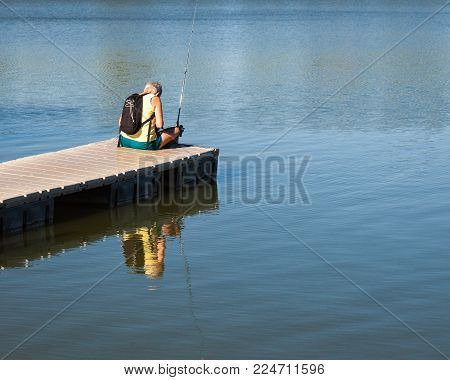 Senior citizen female in plain clothes, fishing from a pier at a lake.