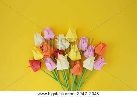 Tulips of origami from multi-colored  paper on a yellow background