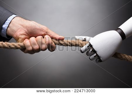 Businessperson And Robot Playing Tug Of War On Gray Background