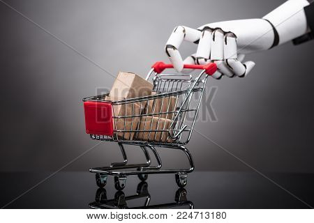 Robot Holding Shopping Cart With Cardboard Boxes On Grey Background