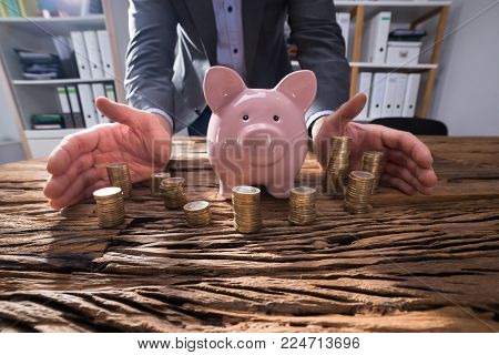Close-up Of A Businessperson's Hand Protecting Stacked Coins And Piggybank On Wooden Desk