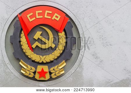 NOVOSIBIRSK, RUSSIA - JULY 18, 2017: Coat of arms, symbols of the former Soviet Union (USSR) - red flag, star, sickle and hammer on a memorial plaque.
