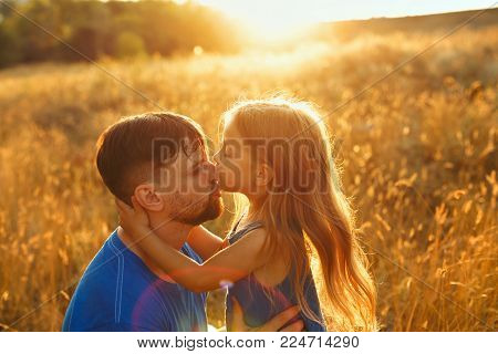 Family values. The daughter kisses her father in the nose. They are walking in the field at sunset. The joy of fatherhood