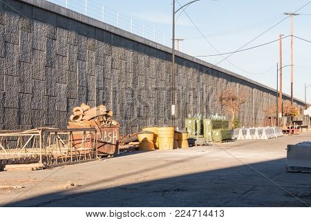 Staging area of road construction materials behide a concrete retaining wall and elevated highway, clear sky, horizontal aspect