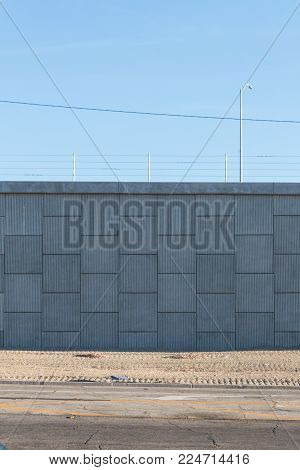 View of street and large block wall of an elevated roadway behind, dirt median, Southern California, copy space, vertical aspect