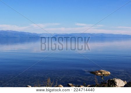 Landscape with the image lake Baikal and the mountains in Buryatia. Warm sunny day in Siberia. Crystal clear water of lake Baikal