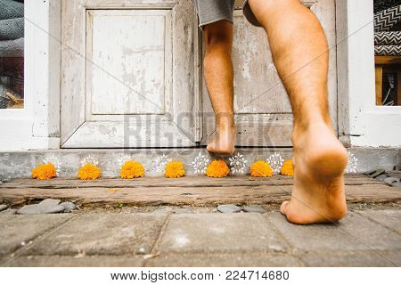 Male bare feet enter the house stepping over the threshold with flowers. The traditional entrance to the house of Asia is decorated with orange flowers.