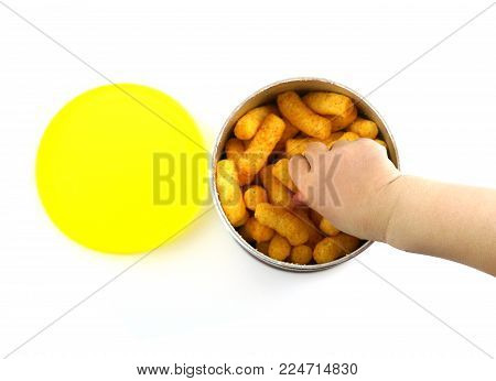 Baby Hand Reaching For Crunch Baked Snack In The Container